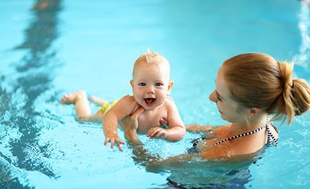 Parent teaching child to swim
